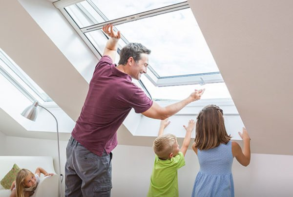 Father accompanied by his children opens a roller screen for roof windows