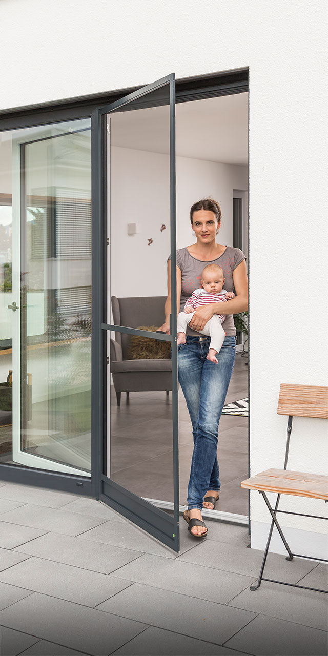 Woman opens hinged frame for door with a baby in her arms