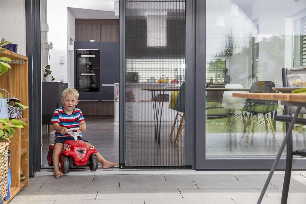 Kinde fährt mit Bobycar durch offene Türe mit halb geöffnetem Plissee