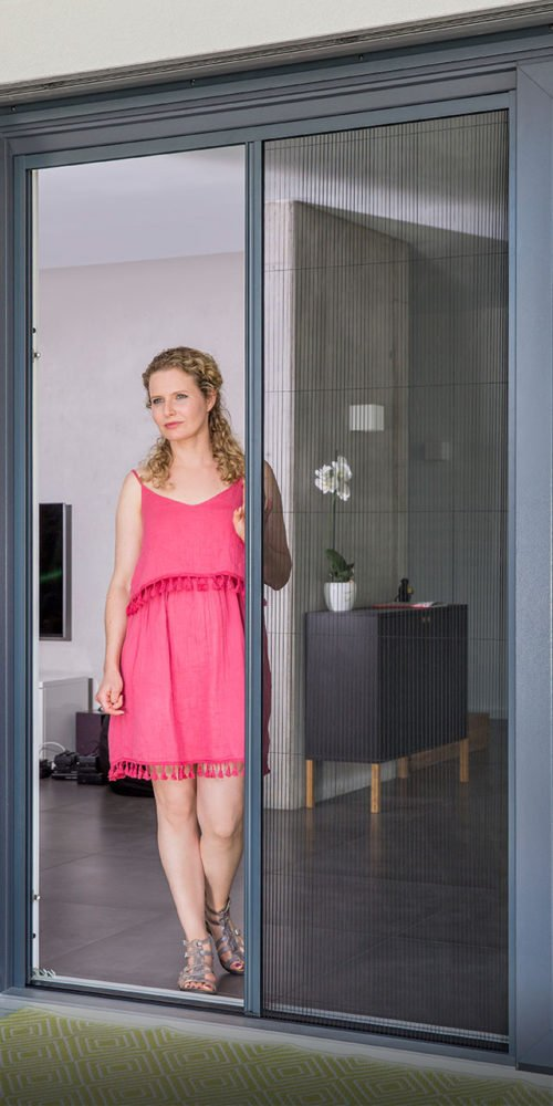Pleated blinds opened by a woman in a pink dress