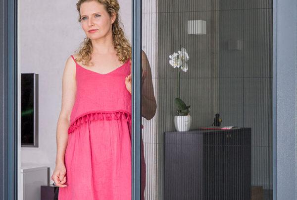 Plissee wird von einer Frau in pinkem Kleid geöffnet