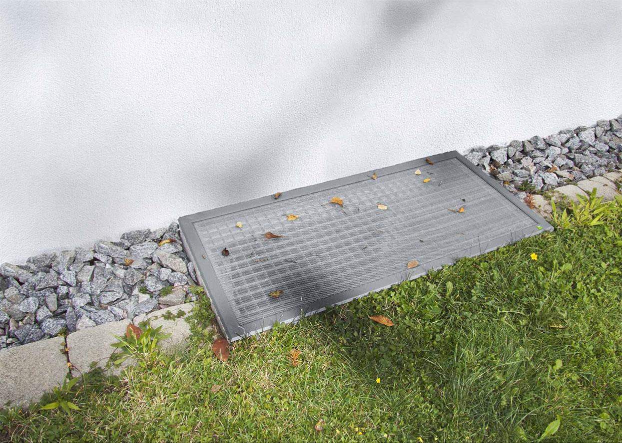Lisa Lichtschachtabdeckung an einer Hauswand mit Gras davor