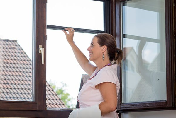 Woman opens insect screening roller screen on window