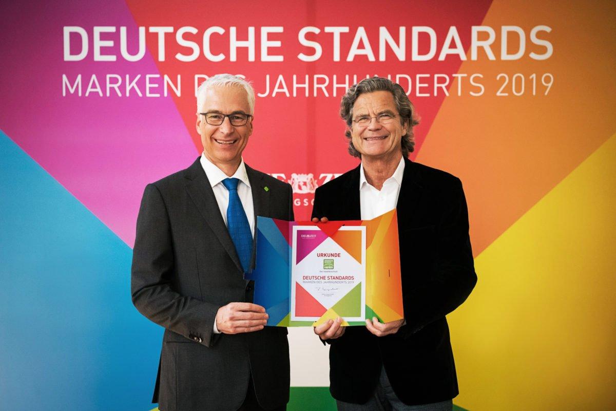 Neher posiert mit Urkunde vor buntem Hintergrund mit Marke des Jahrhunderts 2019
